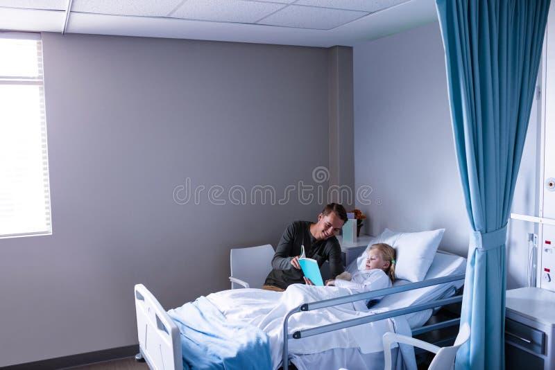 Flicka på en läsebok för sjukhussäng med hennes fader royaltyfria bilder