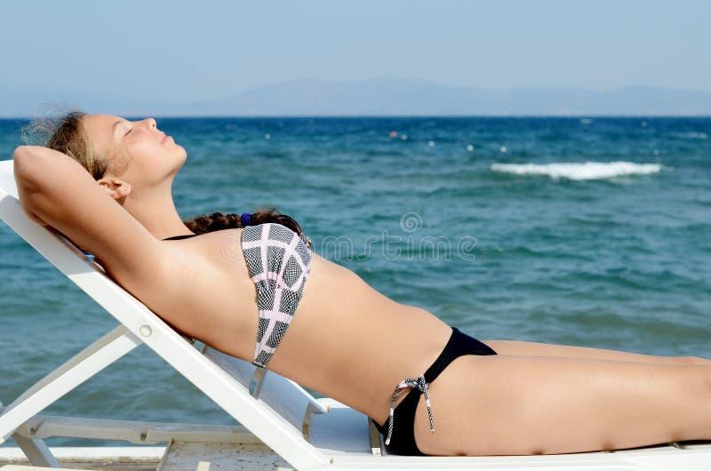 Flicka på en plankasäng på havet royaltyfria foton