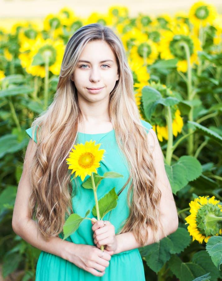 Flicka på fältet av solrosor royaltyfria bilder