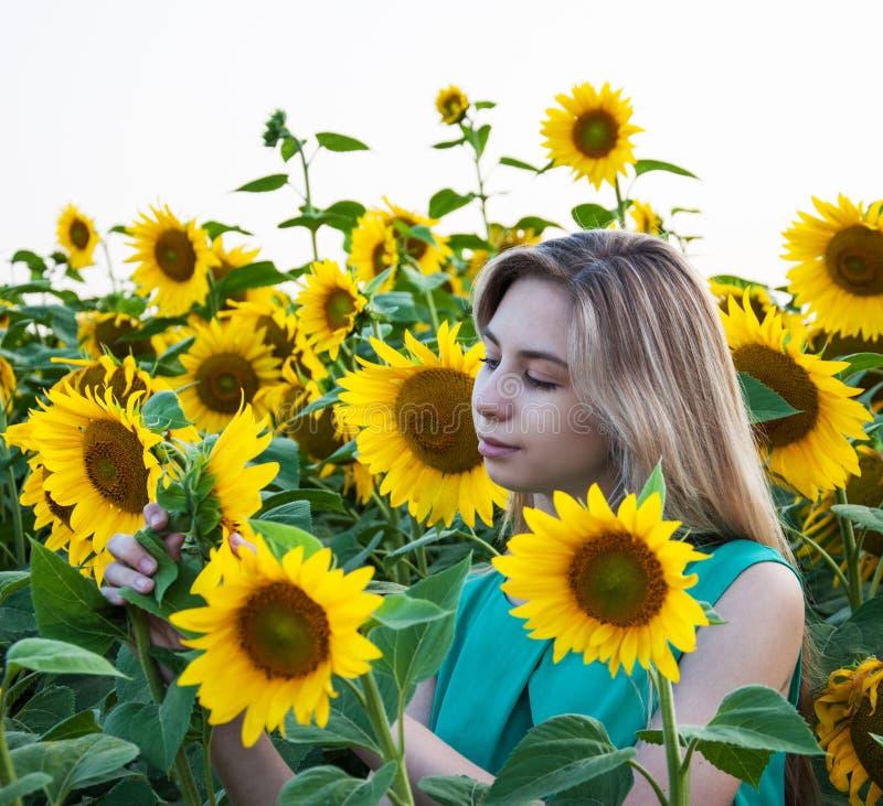 Flicka på fältet av solrosor royaltyfri fotografi