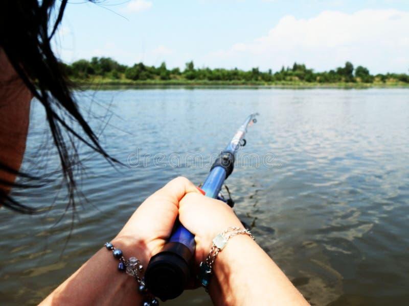 Flicka på floden med en metspö arkivbild