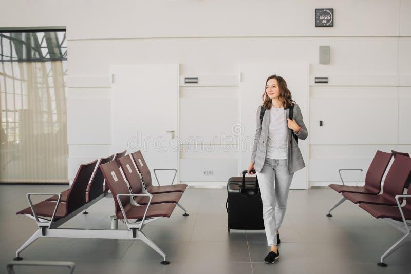 Flicka på flygplatsen som går med hennes bagage royaltyfria bilder