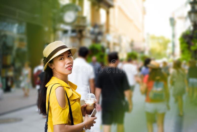 Flicka på gatan med kaffe som går royaltyfri foto