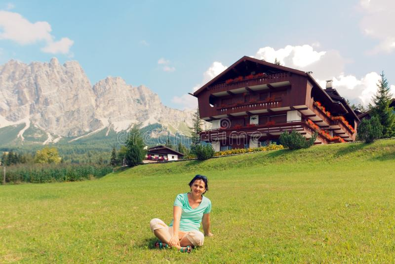 Flicka på gräsmattan nära huset i bergen royaltyfria bilder