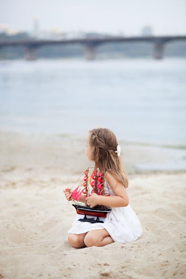 Flicka på havet med ett skepp liten flickaväntanfartyget med scharlakansrött seglar Flickan i det vita brädet på stranden med sch royaltyfri fotografi