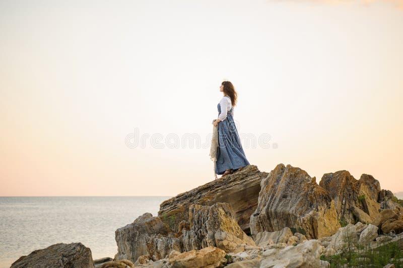Flicka på kanten av en klippa som ut ser till havet arkivbild