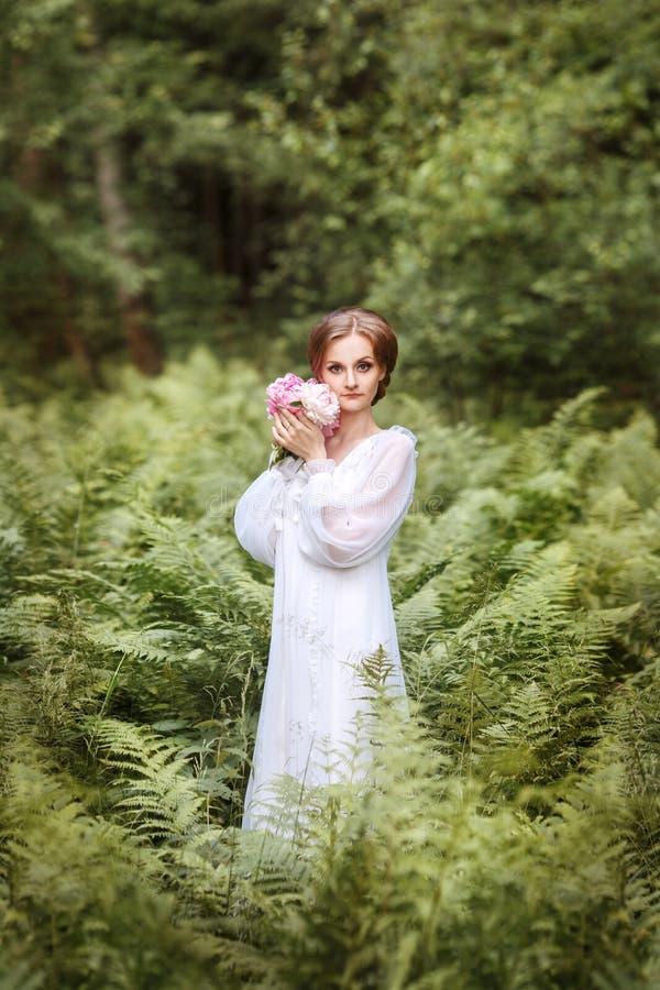 flicka på kanten av skogen i en lång vit klänning royaltyfri bild