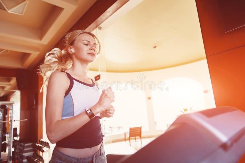 Flicka på morgonkörningen på trampkvarnen i idrottshallen framme av ett stort fönster på bakgrunden av havet royaltyfria foton