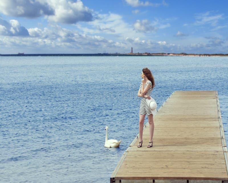 Flicka på pir med svanen arkivfoto