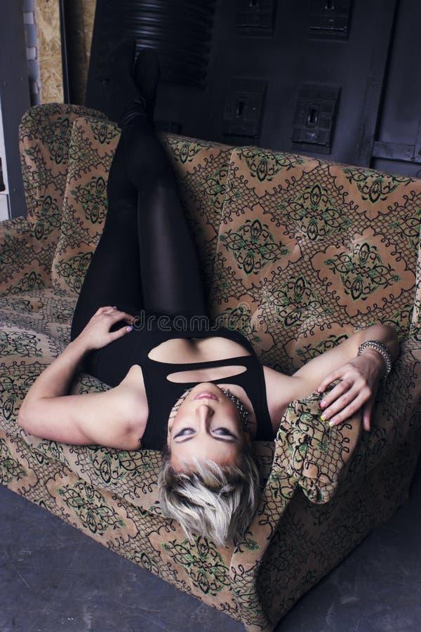 Flicka på rethrosoffan royaltyfria foton