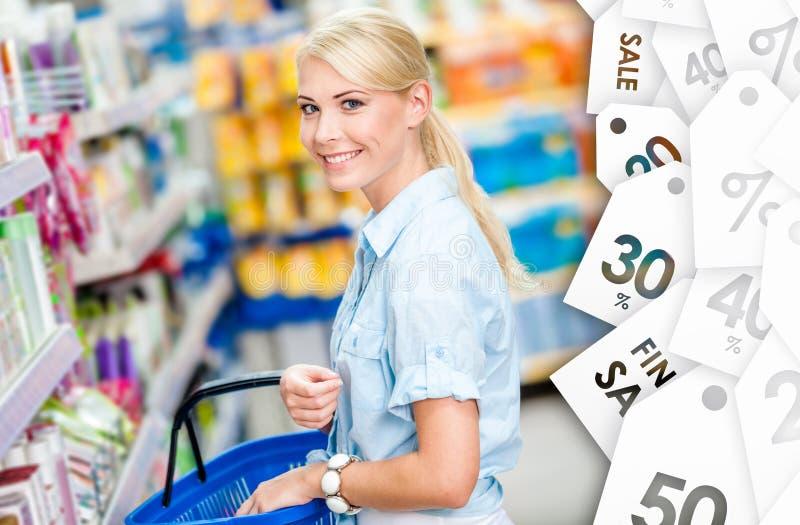 Flicka på shoppa som väljer schampo arkivfoton