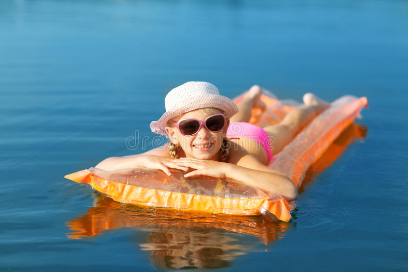 Flicka på simningmadrassen royaltyfria bilder