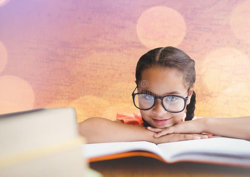 Flicka på skrivbordet med böcker mot översikt med bokeh royaltyfri foto
