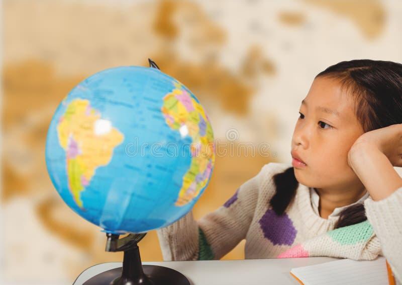 Flicka på skrivbordet med jordklotet mot oskarp brun översikt royaltyfri bild