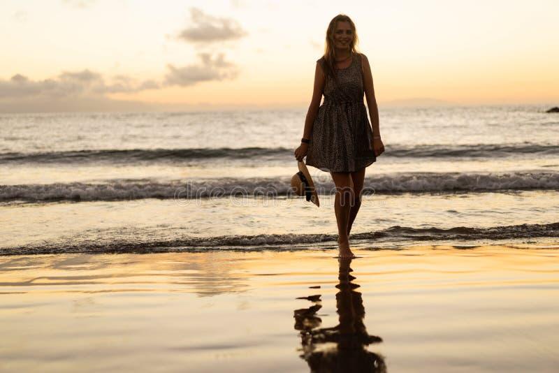 Flicka på solnedgången på stranden arkivfoto