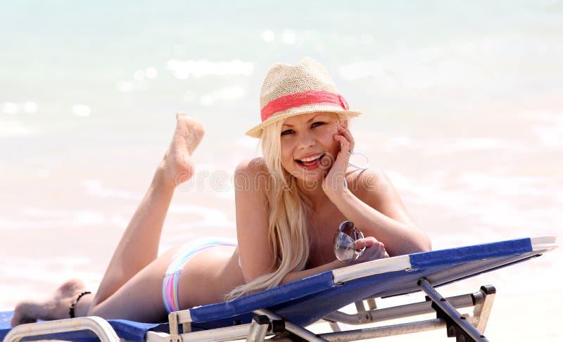 Flicka på stranden. glamorös blondin på semester. lycklig härlig ung kvinna med sommarhatten royaltyfri fotografi