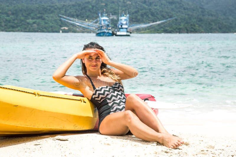 Flicka på stranden med en kanot royaltyfri foto