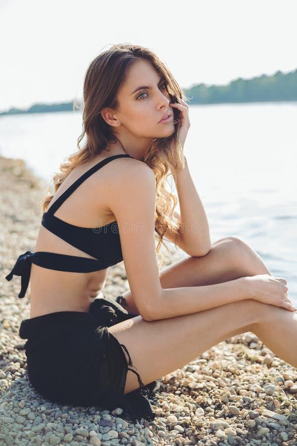 Flicka på stranden som långt borta ser arkivfoton