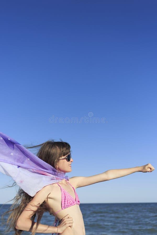 Flicka på stranden som tycker om en ferie på havet arkivbild