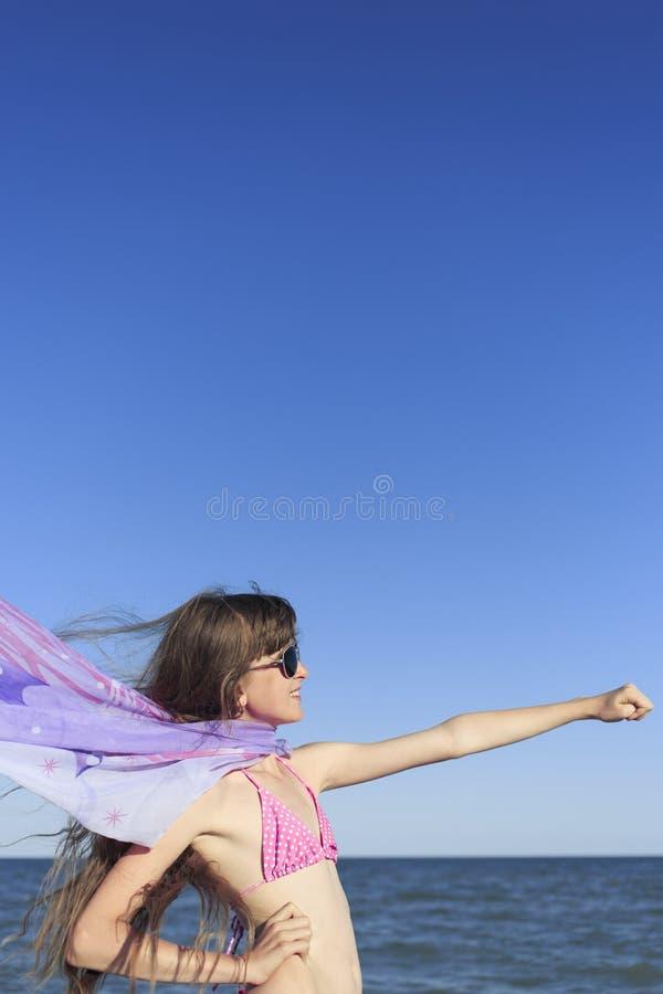 Flicka på stranden som tycker om en ferie på havet arkivfoto