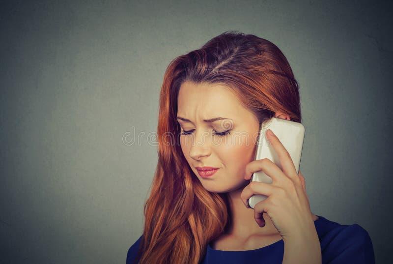 Flicka på telefonen med huvudvärk Uppriven olycklig kvinnlig som talar på telefonen royaltyfri fotografi