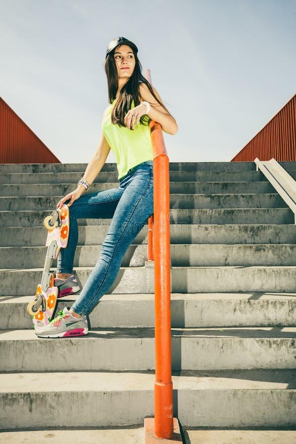 Flicka på trappa med skateboarden arkivfoto