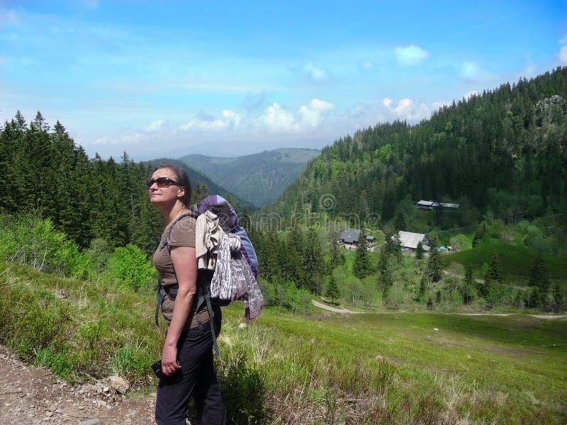 Flicka på vägen i bergen I avståndet moln, himmel, kullar, skogar royaltyfria foton