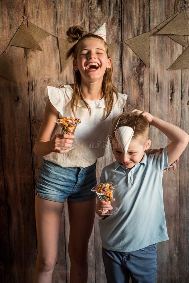 Flicka pojke som delar äta popcorn i en bunke på en trätabellbakgrund Dela begrepp royaltyfri fotografi