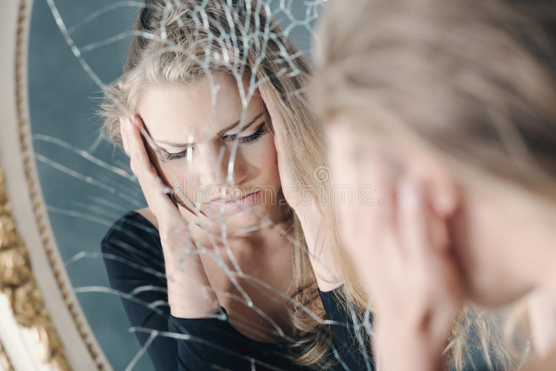 Flicka reflekterad i bruten spegel arkivfoton