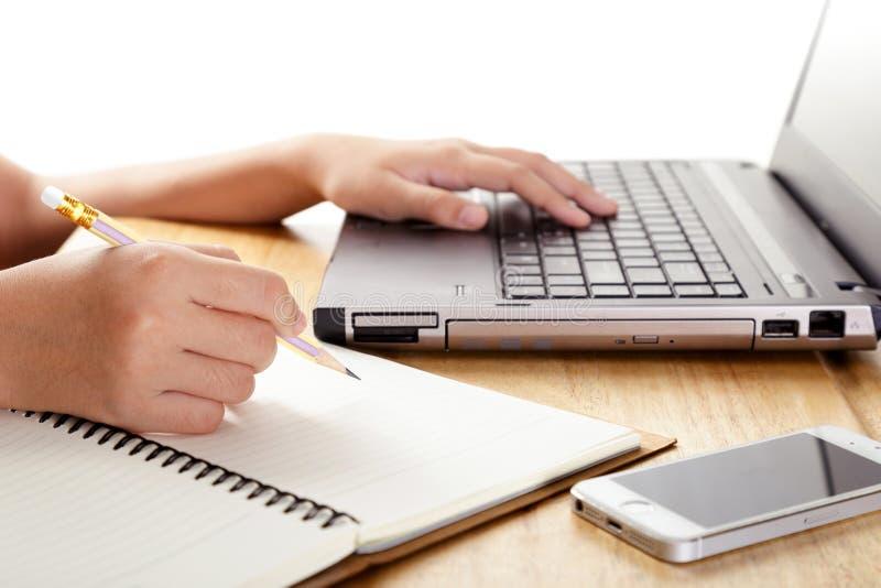 Flicka` s räcker handstil i anteckningsbok och användabärbara datorn arkivbild
