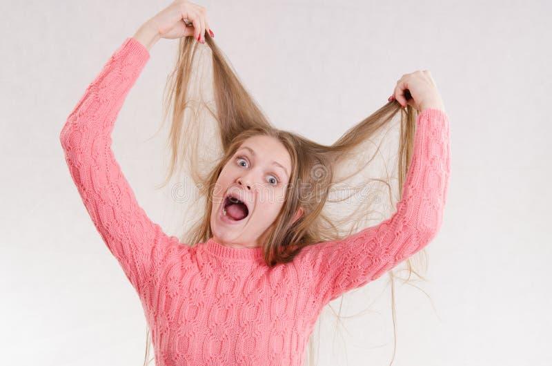 Flicka som är chockad vid hennes hår royaltyfria foton
