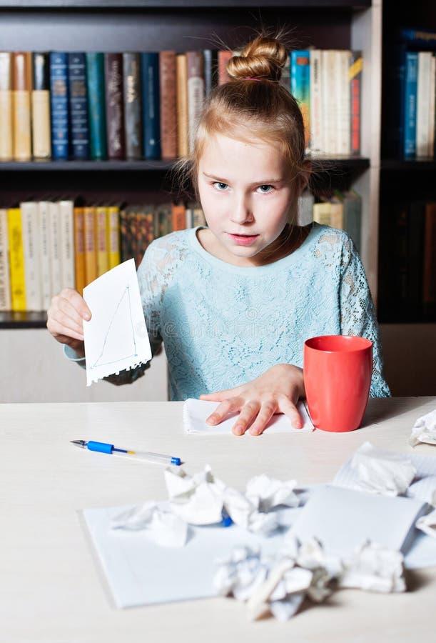 Flicka som är ilsken på tabellen, i händer som skrynklar ett stycke av papper royaltyfri fotografi