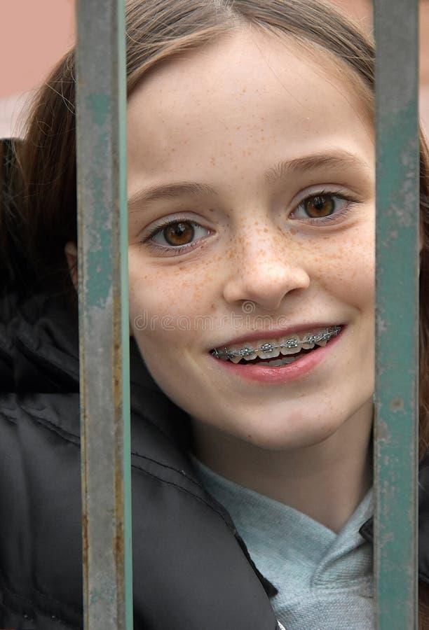 Flicka som är inlåst bak ett staket royaltyfri foto