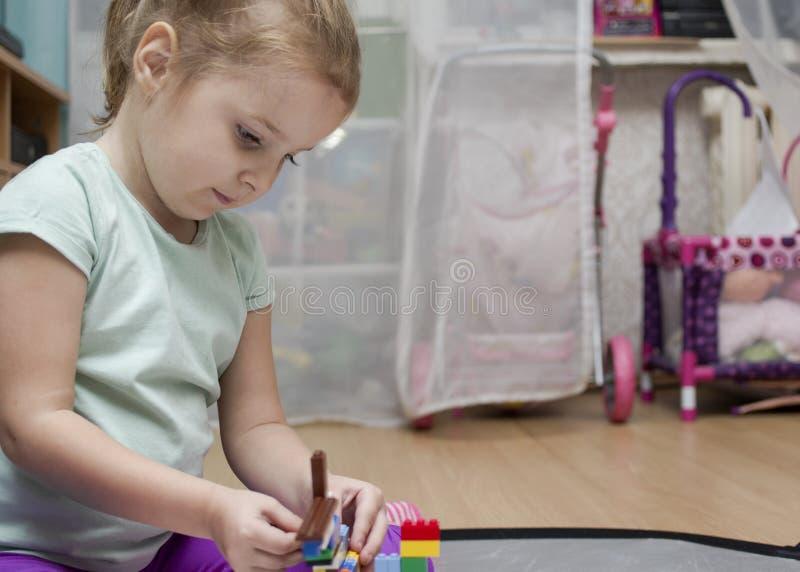 Flicka som är upptagen med leksaker arkivbild