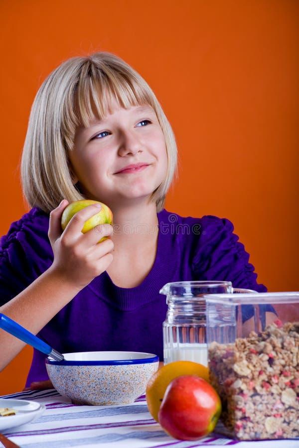 Flicka som äter äpplet royaltyfri bild