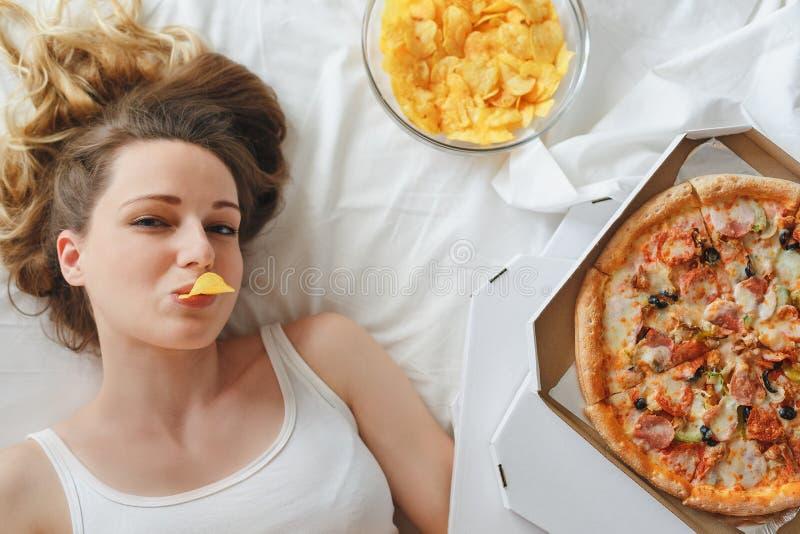 Flicka som äter chiper på sängen som står bredvid pizza arkivbild