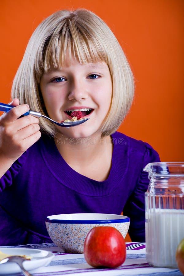 Flicka som äter cornflakes royaltyfri bild