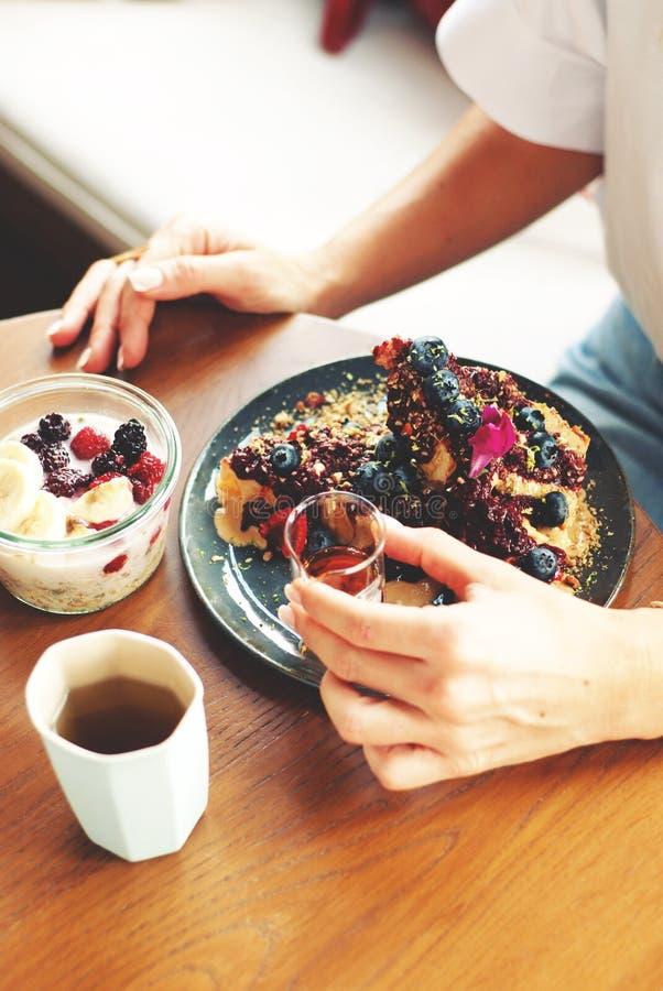 Flicka som äter den sunda frukosten i kafécloseup arkivbild