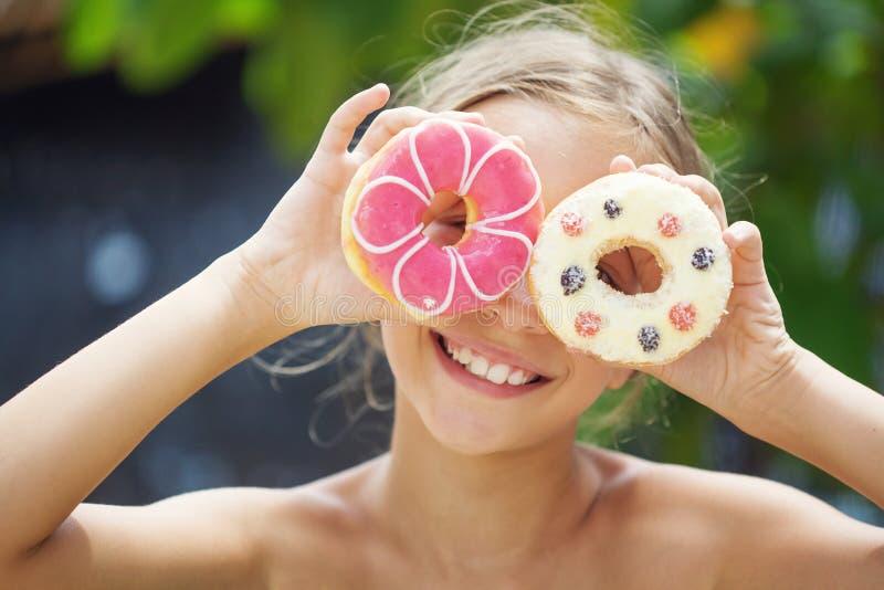 Flicka som äter donuts royaltyfri fotografi
