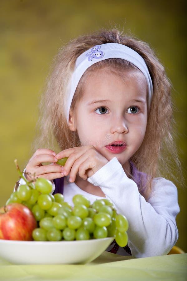Flicka som äter druvor arkivfoto