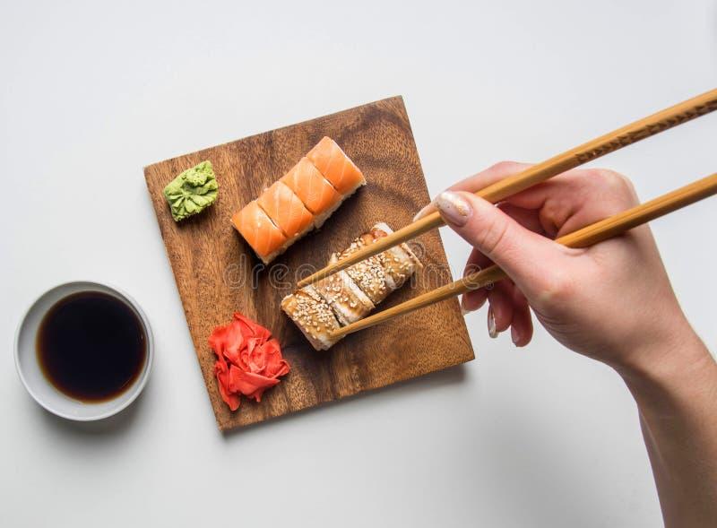 Flicka som äter en aptitretande sushiuppsättning med ingefäran, soya och wasabi på en vit bakgrund arkivfoton