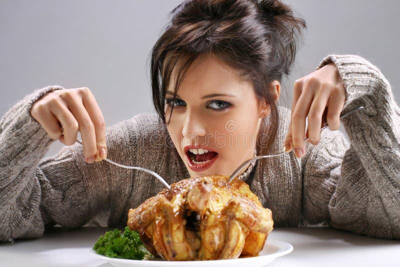 Flicka som äter en höna arkivfoton