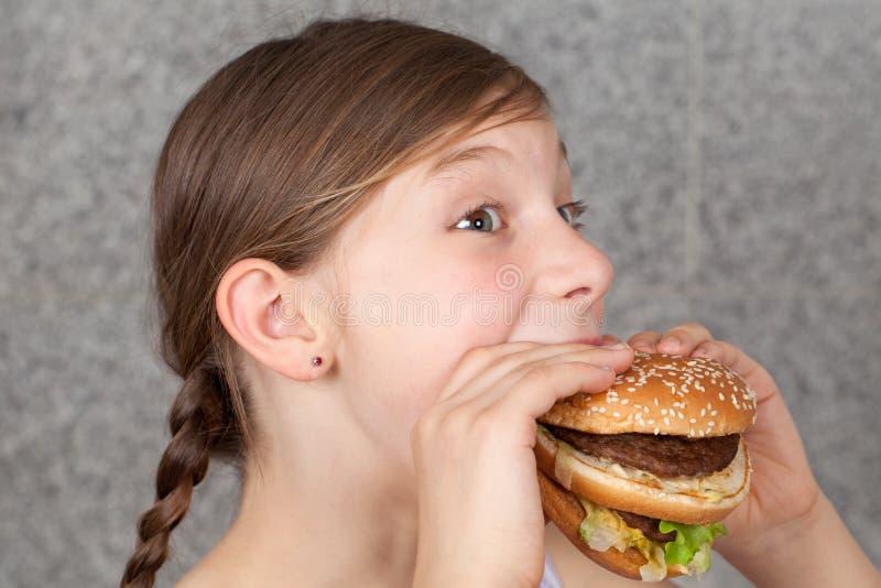 Flicka som äter en hamburgare royaltyfria bilder