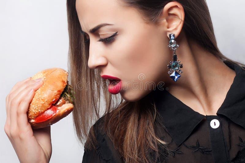 Flicka som äter en stor hamburgare, studiofoto royaltyfri fotografi