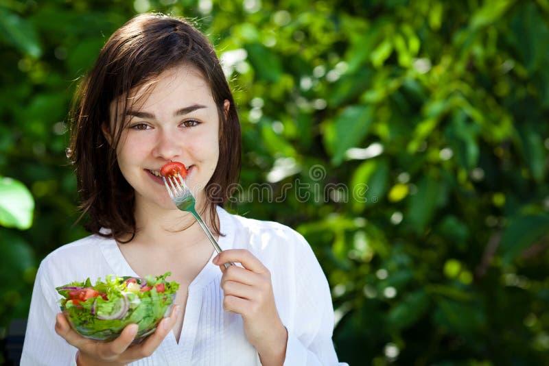 Flicka som äter grönsaksallad arkivbilder