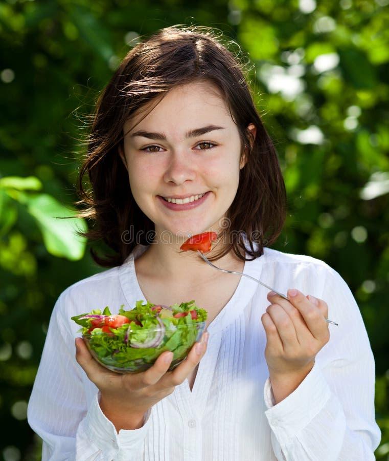 Flicka som äter grönsaksallad arkivbild