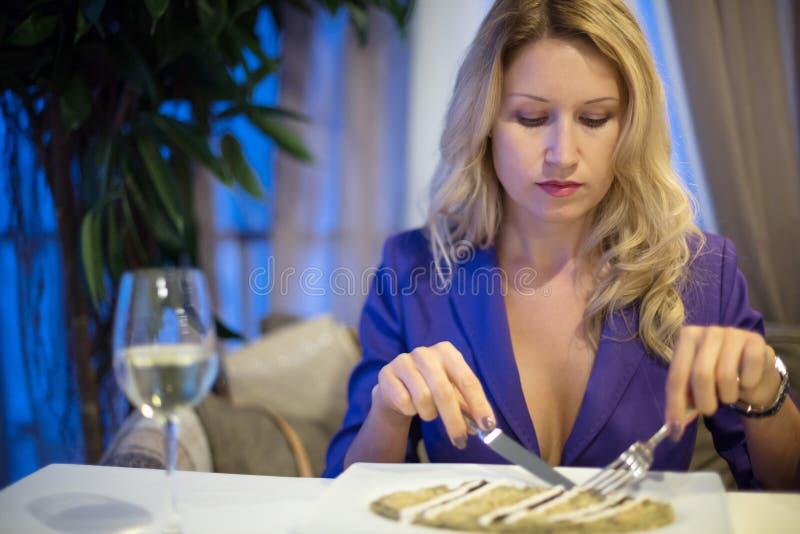 Flicka som äter i en restaurang arkivbild