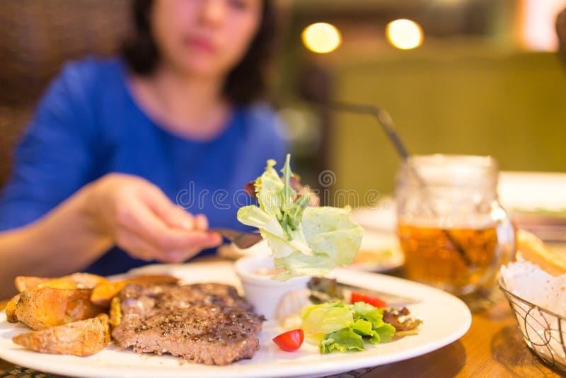 Flicka som äter kött med sallad i en restaurang arkivfoto