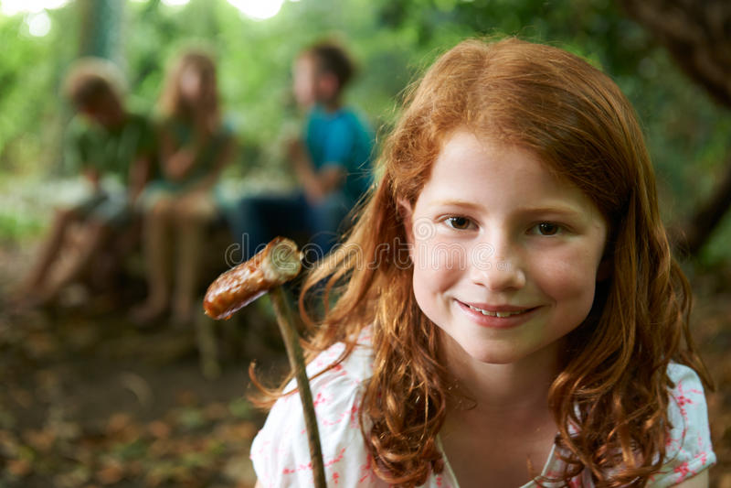 Flicka som äter korven som lagas mat på lägerbrand med vänner arkivfoton