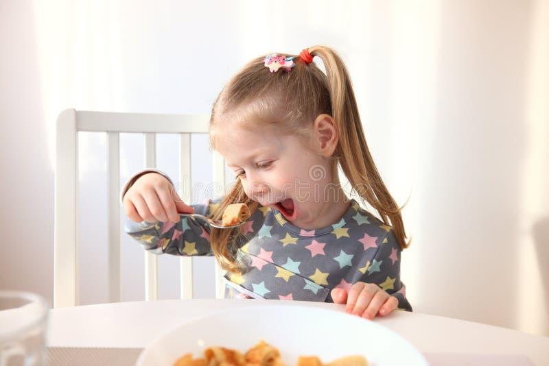 Flicka som äter med aptit Smaklig frukost för barn arkivfoto